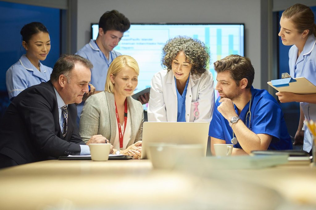 Full medical team reviewing medical scheduling software
